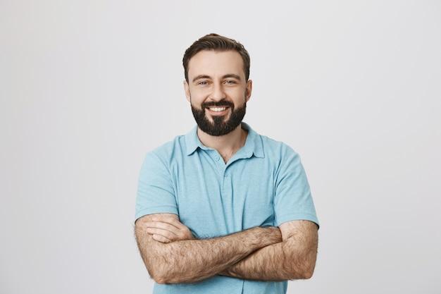 Knappe zelfverzekerde lachende man met handen gekruist op de borst Gratis Foto