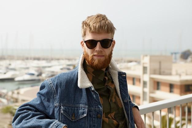 Knappe zelfverzekerde man met fuzzy baard staande op gezichtspunt met armen op witte hek rails Gratis Foto