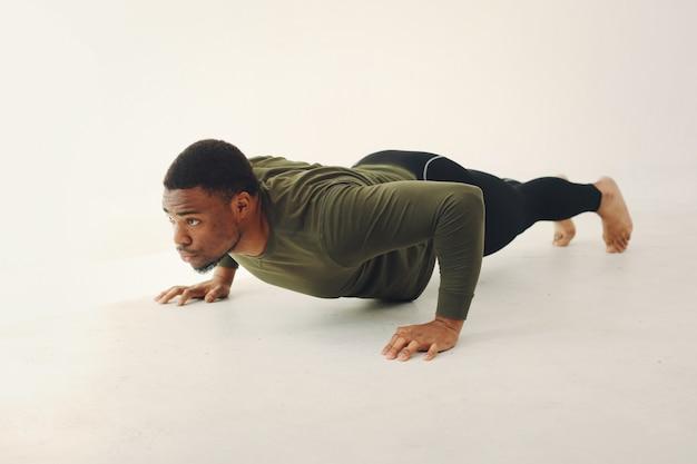 Knappe zwarte man doet yoga op een witte muur Gratis Foto