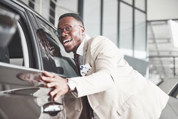 Knappe zwarte man in dealer is zijn nieuwe auto knuffelen en glimlachen. Gratis Foto