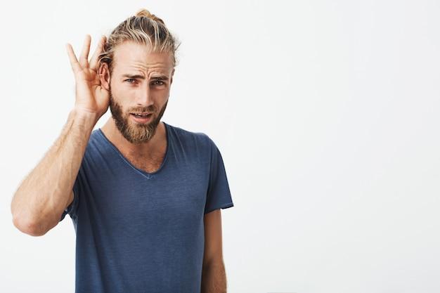 Knappe zweedse man met baard en coole kapsel die hand bij oor houdt Gratis Foto