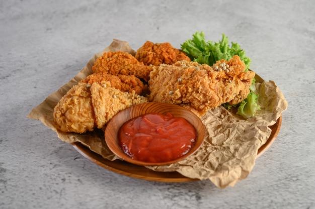 Knapperige gebraden kip op een plaat met tomatensaus Gratis Foto