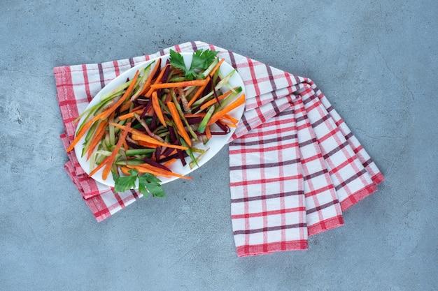 Knapperige wortelen, komkommers en bieten in een snacksalade gehakt op een schaal op marmeren tafel. Gratis Foto