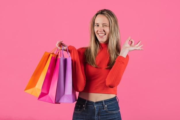 Knipogend meisje met boodschappentassen Gratis Foto