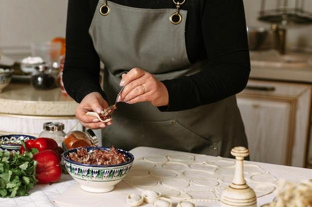 Knoedels, manti en khinkali maken van rundergehakt, lamsvlees en deeg. zelfgemaakt eten Premium Foto