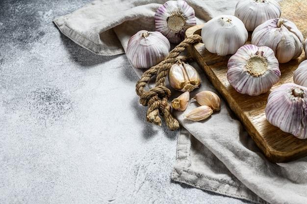 Knoflookbol en knoflookteentjes op een houten snijplank. het concept van gezond eten. grijze achtergrond. bovenaanzicht Premium Foto