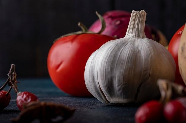 Knoflookhandschoenen en tomaten op zwarte lijst. Gratis Foto