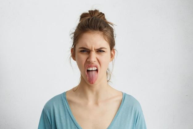 Knorrige vrouw met haarknoop die haar tong toont die negatieve emoties uitdrukt. woedende vrouw die haar walging toont terwijl ze ruzie heeft Gratis Foto