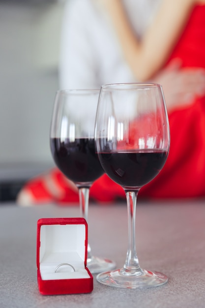 Knuffelen mooi paar. glazen met wijn en doos met ring op tafel Gratis Foto