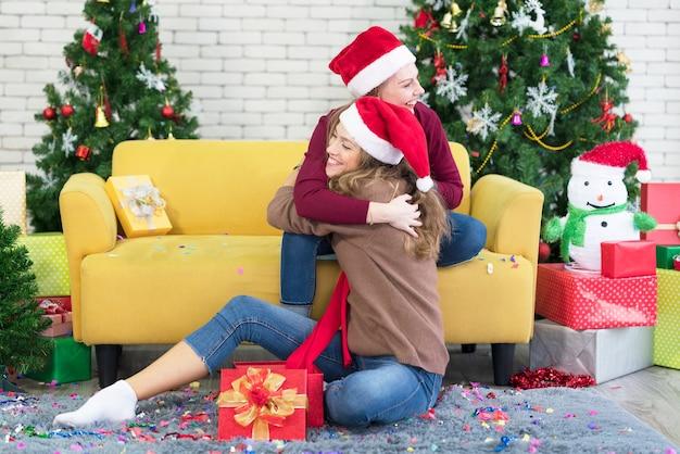 Knuffels vrienden meisjes vriendinnen geven nieuwjaarscadeau in doos, lachend en lachend, naast de kerstboom. Premium Foto