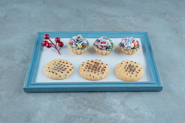 Koekjes, cupcakes en een bessen kerstdecoratie op een bord op marmeren achtergrond. hoge kwaliteit foto Gratis Foto
