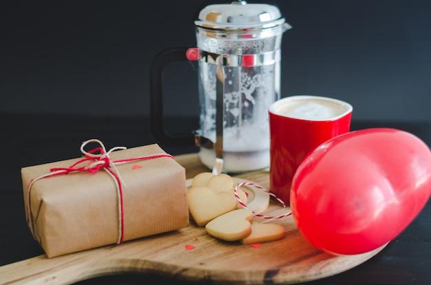 Koekjes en hartvormige ballon, koffiekopje en verpakte doos Premium Foto