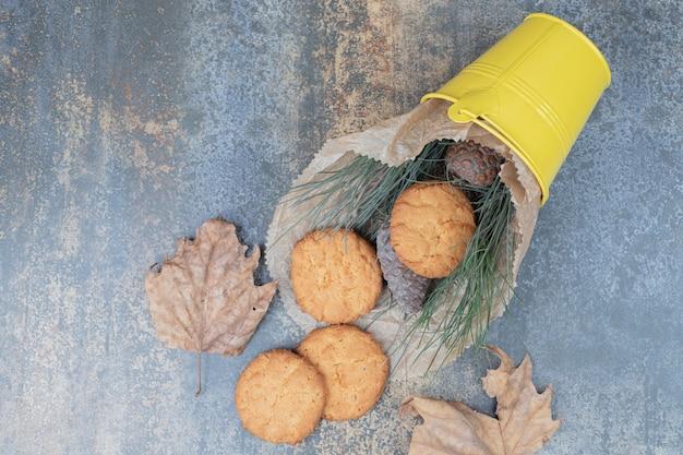 Koekjes, gras en dennenappels in emmer op marmeren tafel. hoge kwaliteit foto Gratis Foto