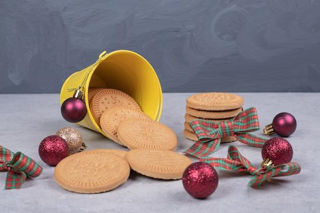 Koekjes in emmer versierd met lint en kerstballen op witte tafel. hoge kwaliteit foto Gratis Foto