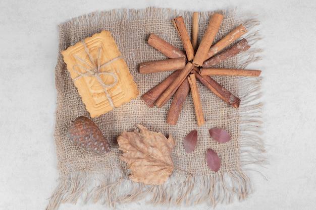 Koekjes in touw met kaneelstokjes, blad en dennenappel op jute. hoge kwaliteit foto Gratis Foto