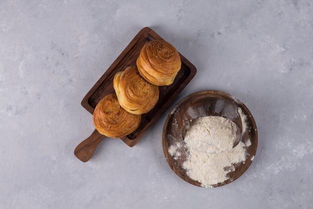Koekjes of broodjes met bloem op een houten schotel, bovenaanzicht Gratis Foto