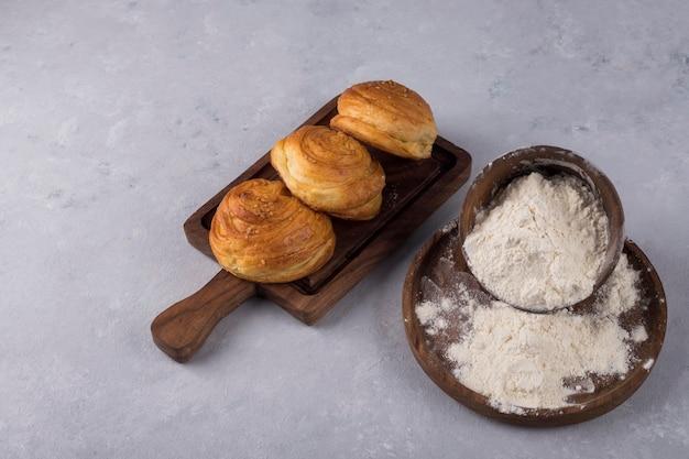 Koekjes of broodjes met bloem op een houten schotel Gratis Foto