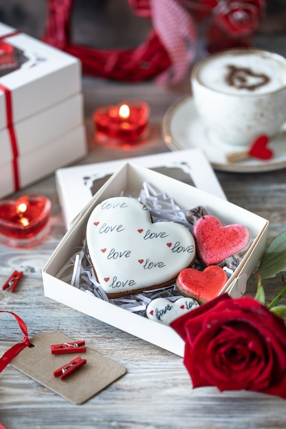 Koekjes of peperkoekkoekjes in een geschenkdoos met een rood lint op een houten tafel. valentijnsdag. Gratis Foto