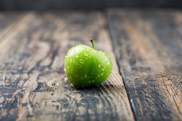 Koel groen pruim zijaanzicht over oude houten muur Gratis Foto
