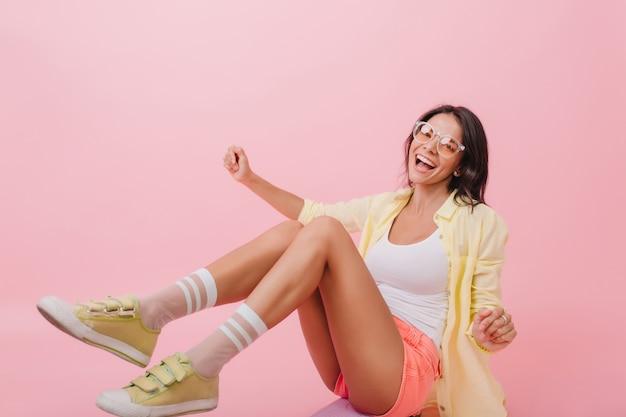 Koel meisje in schattige gele sneakers zittend op de vloer. lieve europese brunette vrouw in lichte outfit ontspannen Gratis Foto
