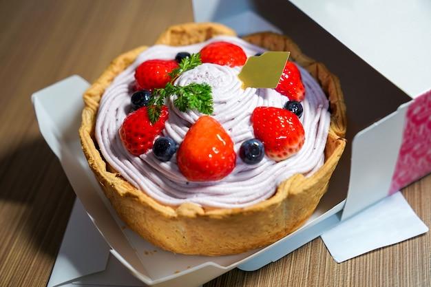 Koel vers fruitig bessenkaastaartje; bosbessenroom als topping met stawberry, bosbessen haal het uit de kartonnen doos. Premium Foto
