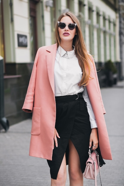Koele jonge stijlvolle mooie vrouw die in straat loopt, roze jas draagt, tas, zonnebril, wit overhemd, zwarte rok, mode-outfit, herfsttrend, gelukkig lachend, accessoires Gratis Foto