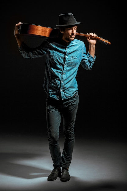 Koele kerel die zich met gitaar op donkere muur bevindt Gratis Foto