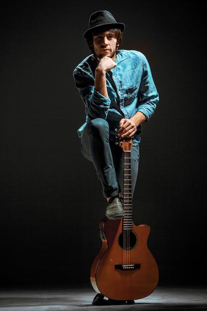Koele kerel die zich met gitaar op donkere ruimte bevindt Gratis Foto