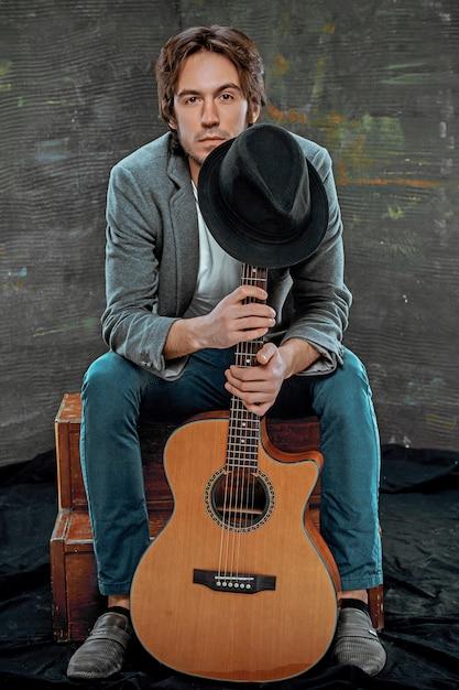 Koele kerelzitting met gitaar op grijze ruimte Gratis Foto
