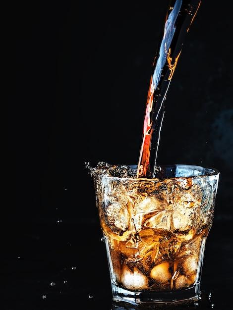 Koele, zachte koolzuurhoudende coladrank wordt in een glas ijs gegoten Gratis Foto