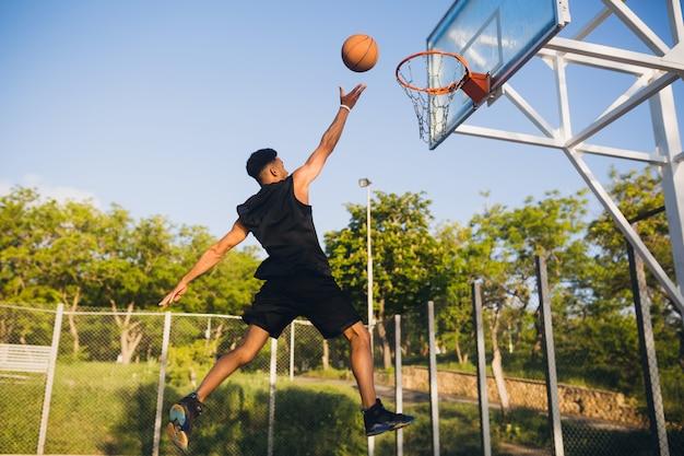 Koele zwarte man die sport doet, basketbal speelt bij zonsopgang, springt Gratis Foto
