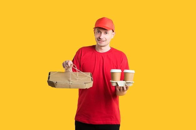 Koerier bezorger in een rode pet en t-shirt houdt dozen en koffie op geel Premium Foto