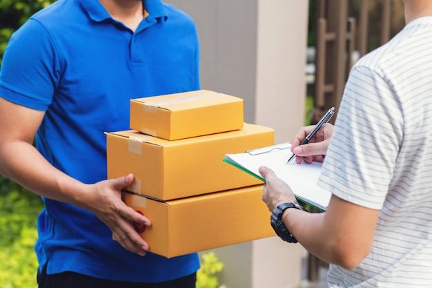 Koeriersdienst, jonge man die pakket ontvangt van een bezorger Premium Foto
