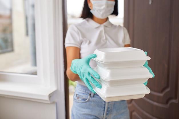 Koeriervrouw houd go box eten, bezorgservice, afhaalrestaurants eten bezorgen aan huisdeur, thuisblijven veilig leven van coronavirus covid-19-uitbraak, bezorgservice onder quarantaine. Premium Foto