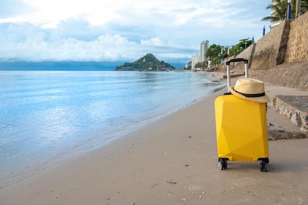 Koffer met hoed op het strand met wolken blauwe hemel, reizend concept. Premium Foto