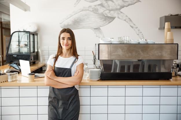 Koffie business owner concept - portret van gelukkige aantrekkelijke jonge mooie kaukasische barista in schort lachend naar de camera in de koffiewinkel counter. Premium Foto
