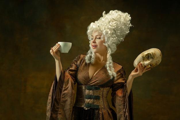 Koffie drinken met masker. portret van middeleeuwse jonge vrouw in bruine vintage kleding op donkere muur. vrouwelijk model als hertogin, koninklijk persoon. concept vergelijking van moderne tijdperken, mode. Gratis Foto