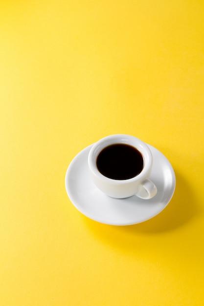 Koffie espresso in kleine witte keramische beker op gele levendige achtergrond Gratis Foto