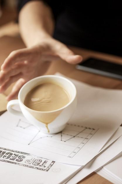 Koffie in witte kop die op de lijst in de ochtend bij bureaulijst morsen Gratis Foto