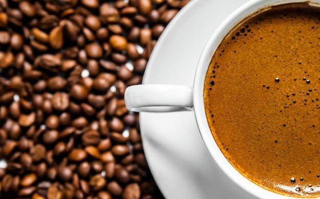 Koffie kopje en koffiebonen op tafel, bovenaanzicht, liefde koffie, bruine koffiebonen geïsoleerd op witte achtergrond, warme koffie kopje koffiebonen Gratis Foto