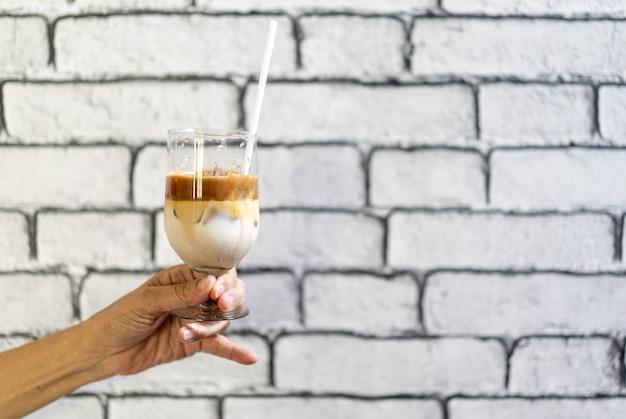 Koffie macchiato en melklaag met ijs in champagneglas werd door aziatische grootmoeder hand voor wit bakstenen muurbehang gehouden. Premium Foto