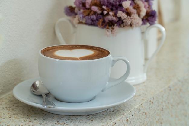 Koffie met hartvormig melkschuim dichtbij venster met een vaas met droge bloem. Premium Foto