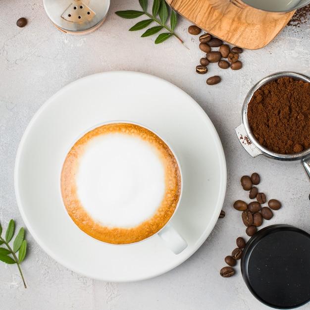 Koffie met lattekunst in een witte ceramische kop op een lijst Gratis Foto