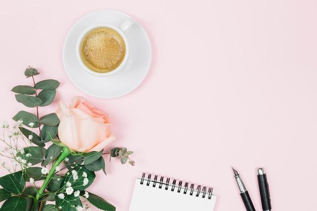 Koffie; roos; kladblok en vulpen op roze achtergrond Gratis Foto