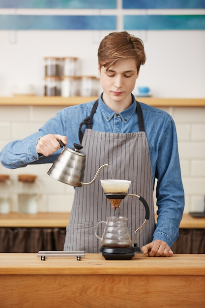 Koffie schenken. leuke barista die koffiedrank voorbereidt, geconcentreerd kijkt. Gratis Foto