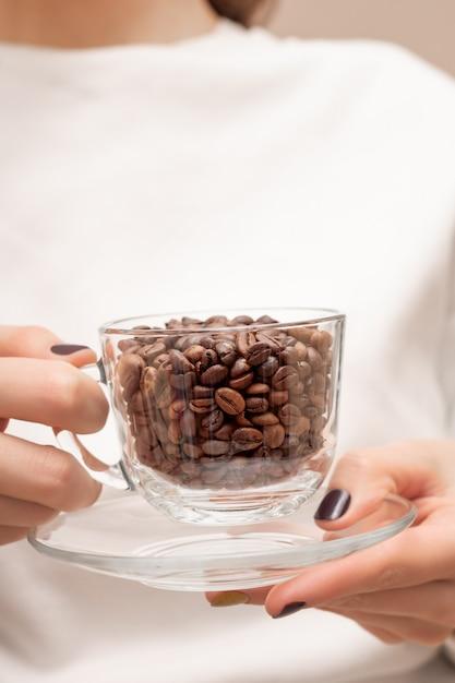 Koffiebonen in een glazen beker op vrouwelijke handen. Gratis Foto