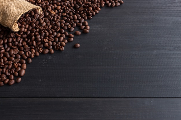 Koffiebonen in jutezak op oude houten met zacht-nadruk en meer dan licht op de achtergrond Premium Foto