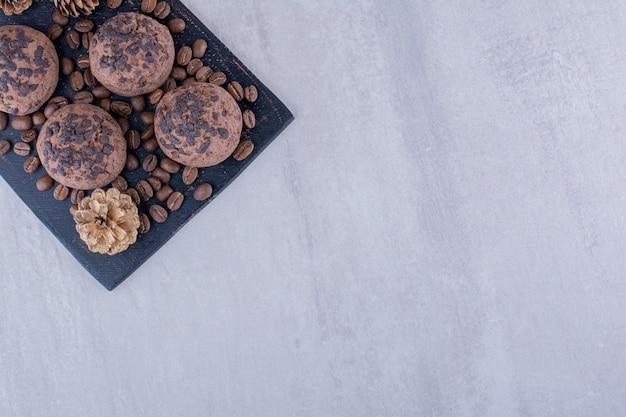 Koffiebonen, koekjes en een dennenappel op witte achtergrond. Gratis Foto