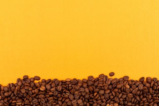 Koffiebonen met exemplaarruimte op gele oppervlakte Gratis Foto