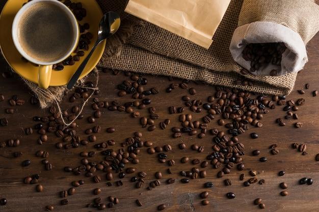 Koffiebonen op bureau met zak en kop worden geplaatst die Gratis Foto